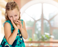 Little girl holding in hands a small turtle. Royalty Free Stock Image