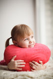 Little girl holding heart-shaped pillow. Valentines day. Mothers Stock Photography