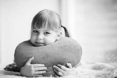 Little girl holding heart-shaped pillow. Valentines day. Mothers Royalty Free Stock Photo