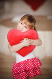 Little girl holding heart-shaped pillow. Valentines day. Mothers Stock Photo