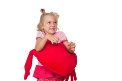 Little girl holding a heart shaped pillow Stock Photos