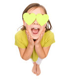 Little girl is holding hearts over her eyes Royalty Free Stock Image
