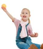 Little girl holding her at arm's length apple. Stock Photo