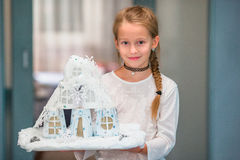 Little girl holding her craft cardboard house. Happy home concept. Royalty Free Stock Images
