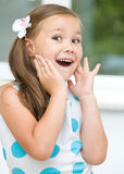 Little girl is holding her face. While listening to somebody Stock Photos