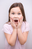 Little girl is holding her face Stock Image