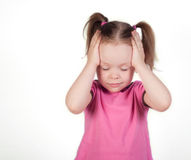 Little girl holding her head Stock Images