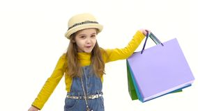 Little girl holding her purchases and surprised them. White background. Slow motion stock video