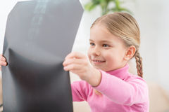 Little girl holding her radiogram. Interesting thing. Positive curious little girl holding her radiogram and attentively examining it while expressing gladness Royalty Free Stock Images