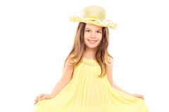 Little girl holding her yellow dress Royalty Free Stock Image