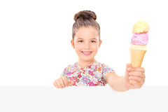 Little girl holding an ice cream behind billboard Royalty Free Stock Photos