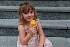 Little girl holding an ice cream cone. Pretty little girl in summer dress sitting in exterior staircase smiling while holding an ice cream cone Royalty Free Stock Image