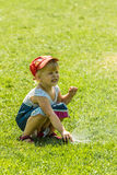 Little girl holding during irrigation, spray. On the grass royalty free stock photos