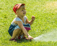 Little girl holding during irrigation, spray. On the grass Stock Photos