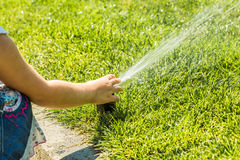 Little girl holding during irrigation, spray. On the grass royalty free stock images
