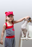 Little girl holding Jack Russell terrierjaws Royalty Free Stock Photo