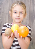 Little girl holding kiwi, lemon and orange Stock Photos