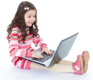 Little girl holding a laptop on his knees. And fun smiling at the camera.Isolated on white background Royalty Free Stock Photography