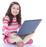 Little girl holding a laptop on his knees. And fun smiling at the camera.Isolated on white background Stock Photos