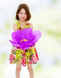 Little girl holding a large purple flower Royalty Free Stock Images