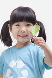 Little girl holding leaf, close up studio shot Royalty Free Stock Photo