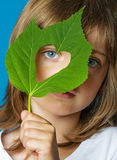 Little girl holding a leaf with heart shape Royalty Free Stock Photos