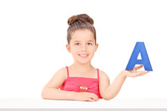 Little girl holding the letter a seated at a table Stock Photos