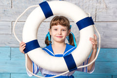 Little girl holding a lifebuoy and laughing Stock Photo
