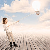 Little girl holding a light bulb with a rope Royalty Free Stock Photo