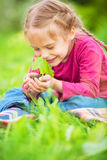 Little girl holding little green plant in her hands Royalty Free Stock Photo