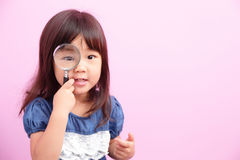 Little girl holding magnifying Stock Photos