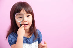 Little girl holding magnifying Stock Photography