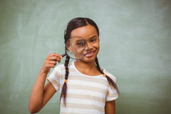 Little girl holding magnifying glass in classroom Royalty Free Stock Image
