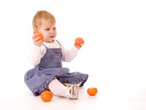 Little girl holding mandarines Stock Photography