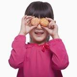 Little girl holding mandarins in front of her eyes, studio shot Stock Image