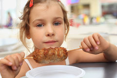 Little girl holding meat on stick Royalty Free Stock Image