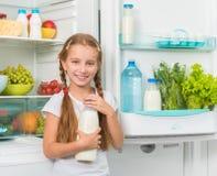 Little girl holding milk near fridge Royalty Free Stock Photos