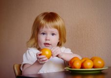 Little girl holding orange. Redhead little girl holding orange Royalty Free Stock Photography