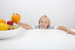 Little girl holding orange from fruit bowl at table Stock Photography