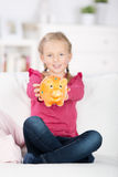 Little Girl Holding Out Piggy Bank Stock Images