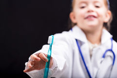 Little girl holding out a toothbrush to the viewer Stock Image