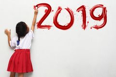 Little girl holding a paint brush painting happy new year 2019 stock photography