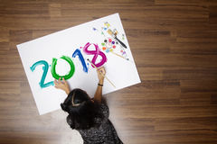 Little girl holding a paint brush painting happy new year 2018 Royalty Free Stock Photos