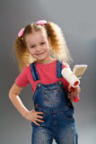 Little girl holding paint brush and roller Royalty Free Stock Photos