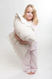 Little girl holding a pillow. Cute little blonde girl in her pajamas holding a pillow Stock Photos
