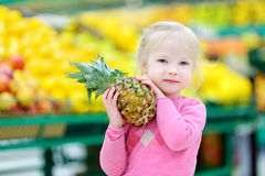 Little girl holding a pineapple in a food store Stock Photo