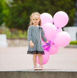 Little girl holding pink balloons Royalty Free Stock Photos