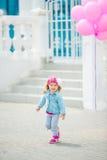 Little girl holding pink balloons Stock Image