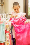 Little girl holding pink dress in hands Royalty Free Stock Image