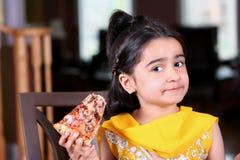 Little girl holding a pizza slice. Little girl in east indian clothes holding a pizza slice stock image